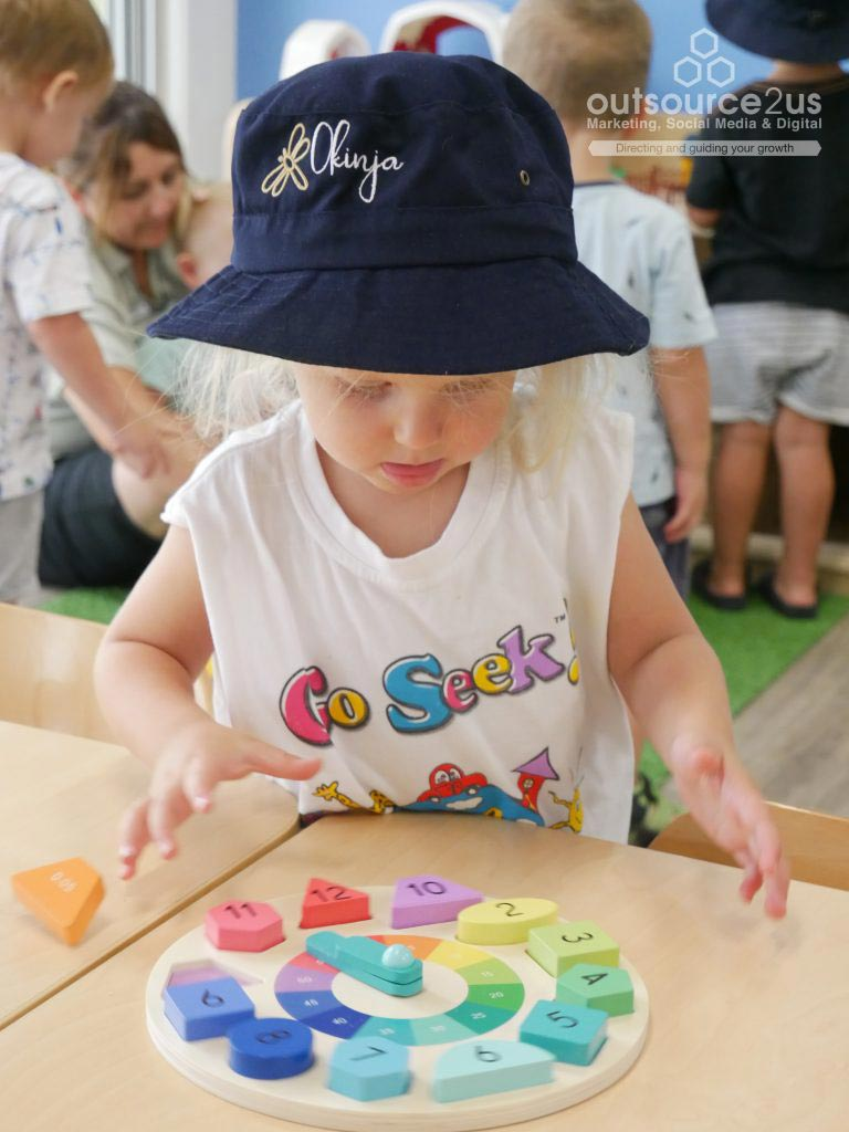 Little girl playing with colorful toy clock - Outsource To Us